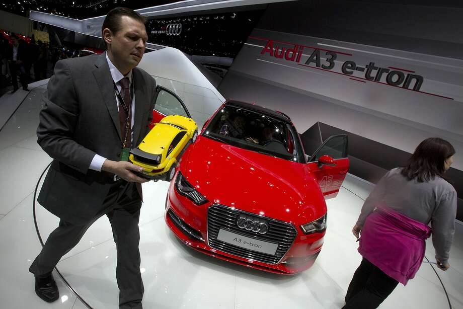 A man holds a scaled model of a Audi car as he walks past the Audi A3 e-tron displayed at the China Auto show in Beijing, China, Sunday, April 20, 2014. Photo: Ng Han Guan, Associated Press