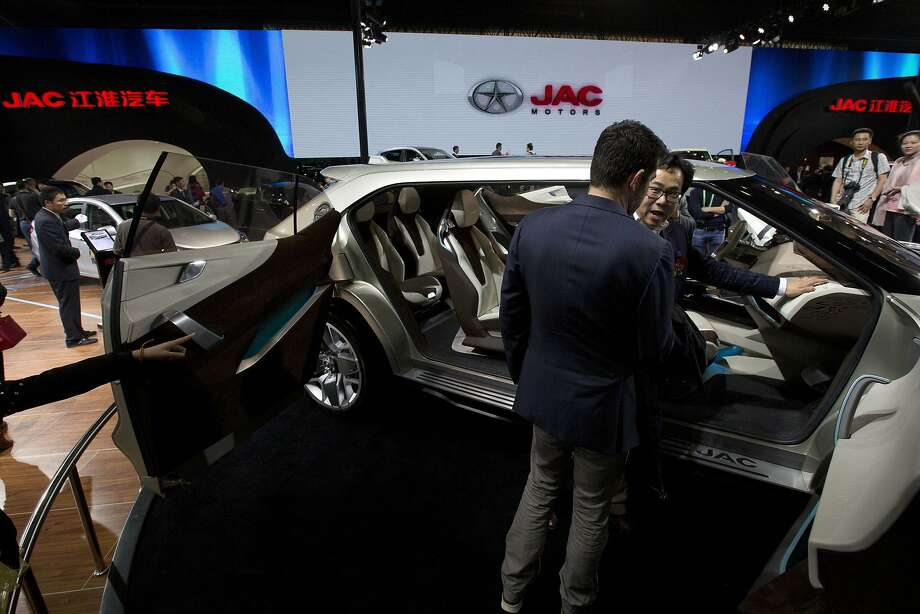 Visitors take a closer look at the SC9 concept car from Chinese automaker JAC displayed at the China Auto show in Beijing, China, Sunday, April 20, 2014.  Photo: Ng Han Guan, Associated Press