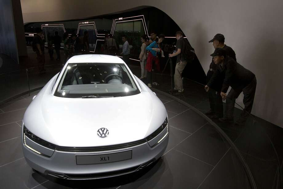 Visitors look at the XL1 concept car from Shanghai Volkswagen displayed at the China Auto show in Beijing, China, Sunday, April 20, 2014.  Photo: Ng Han Guan, Associated Press