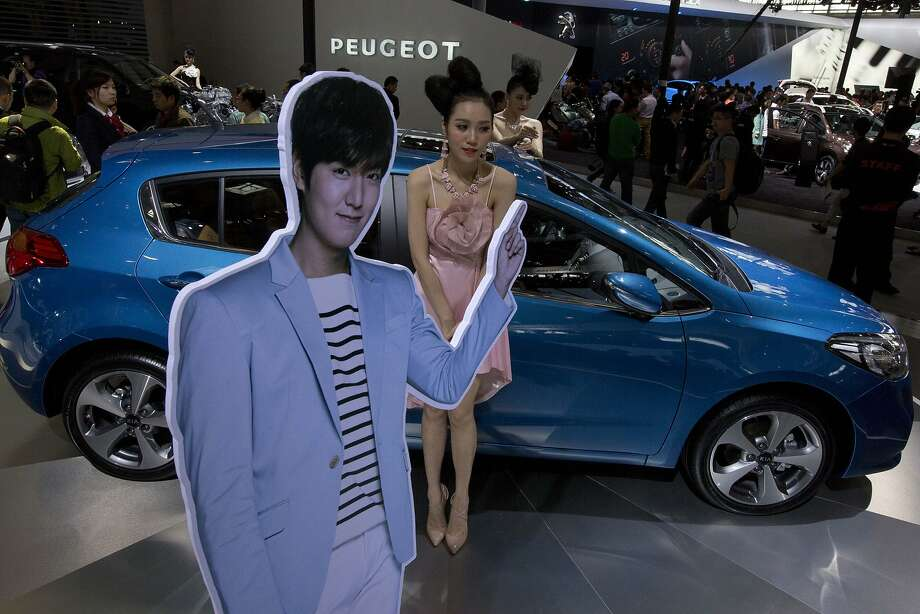 Car models pose next to a Kia Motors K3S sedan and a cut out of brand ambassador and South Korean actor Lee Minho displayed at the China Auto show in Beijing, China, Sunday, April 20, 2014. Photo: Ng Han Guan, Associated Press