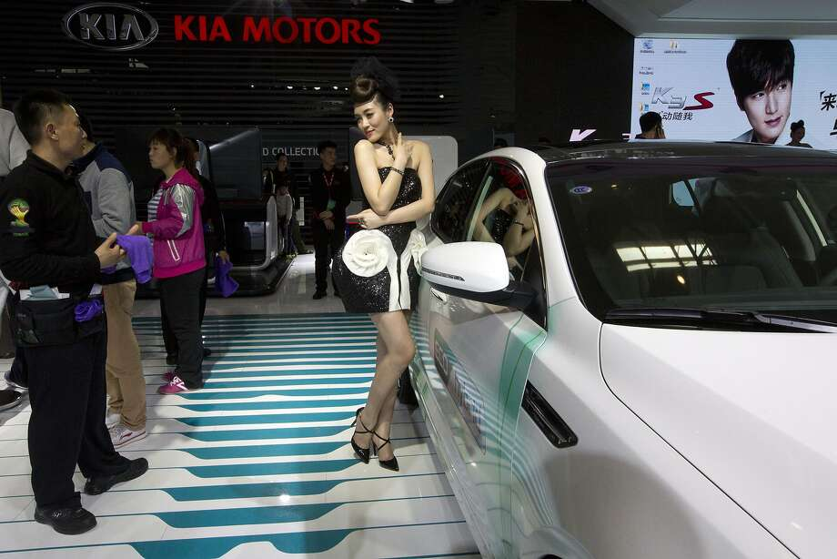 A car model poses next to a car from Kia Motors displayed at the China Auto show in Beijing, China, Sunday, April 20, 2014.  Photo: Ng Han Guan, Associated Press