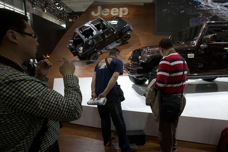 Chinese men look at Jeep models displayed during the China Auto show in Beijing Sunday, April 20, 2014. Photo: Ng Han Guan, Associated Press