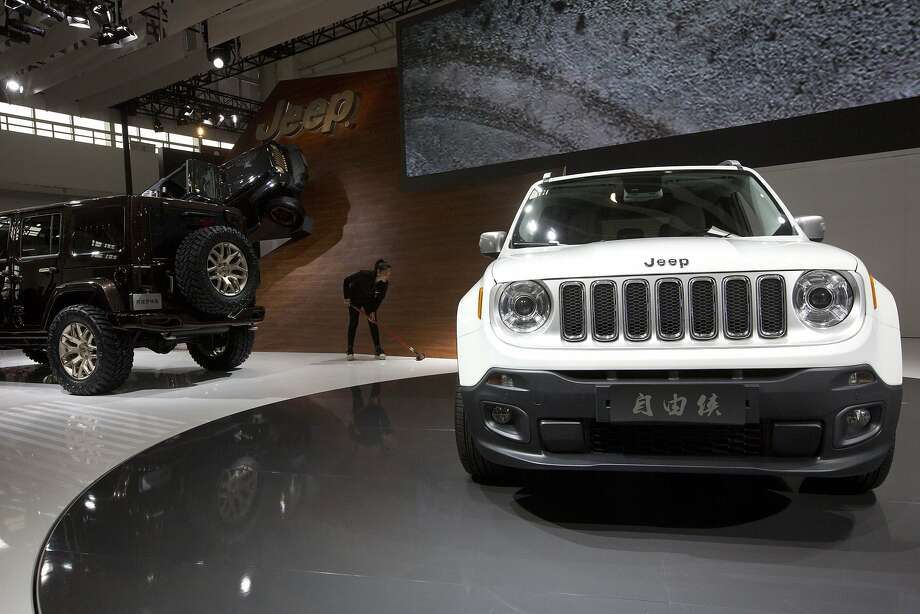 A worker cleans the floor near a Jeep Renegade that's aimed at China's booming market for sport utility vehicles at right during the China Auto show in Beijing Sunday, April 20, 2014. Photo: Ng Han Guan, Associated Press