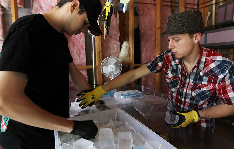 Jake Corney (left) and Andrew Hack pack ice cubes at their business, H&C Ice. They are bringing their experience as bartenders to their business of providing quality ice cubes to bars. Photo: Photos By Jerry Lara / San Antonio Express-News / © 2014 San Antonio Express-News