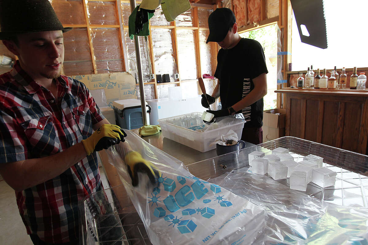 Andrew Hack, left, and Jake Corney, work on packing ice cubes at their business, H&C Ice, Tuesday, April 22, 2014. Bartenders, Corney, who works with Bohanan's, and Hack who works at Minnie's Tavern, sell the 2 and 2 and a quarter inch squares of ice to several restaurants and bars in town.