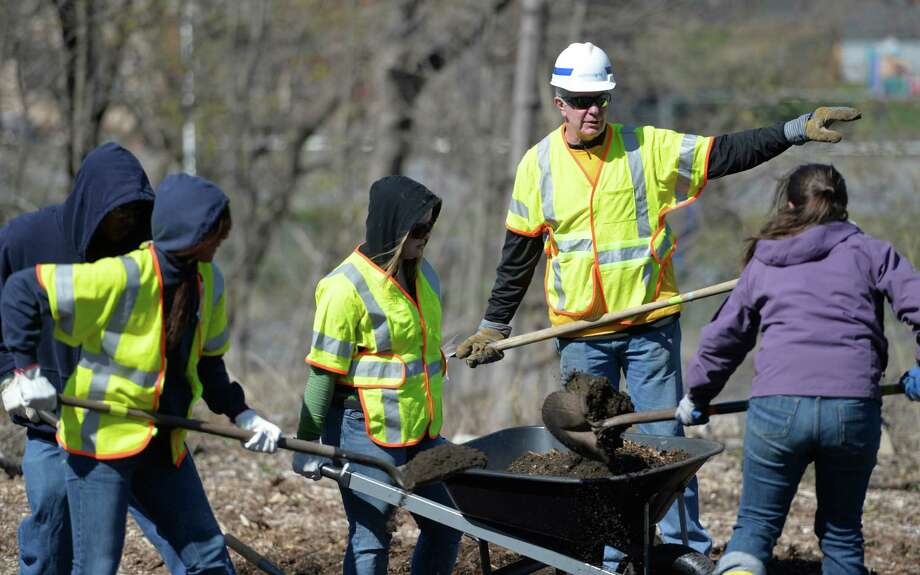 Bill Flaherty, National Grid director of community and customer management, second from right gets his hands dirty with a sizable crew from National Grid at the Capital District Community Garden Thursday morning April 24, 2014 in Troy, N.Y.  as part of their Earth Day volunteer program.       (Skip Dickstein / Times Union) Photo: SKIP DICKSTEIN / 00026610A