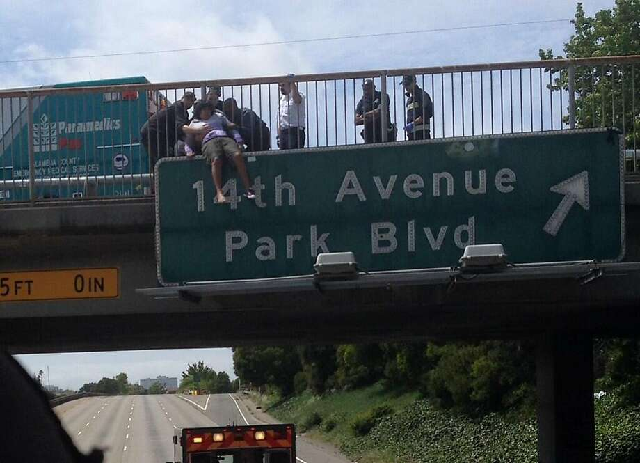 Rescuers restrain a despondent man on an Interstate 580 overpass. A landscaper on his way home saw him and talked with him until help arrived. Photo: Courtesy Of The Oakland Fire Dep
