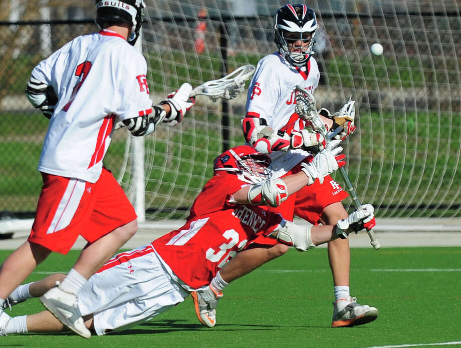 Greenwich's Alec Oropall pass the ball as he falls, during boys lacrosse action against Fairfield Prep at Fairfield University in Fairfield, Conn. on Thursday April 24, 2014. Photo: Christian Abraham / Connecticut Post