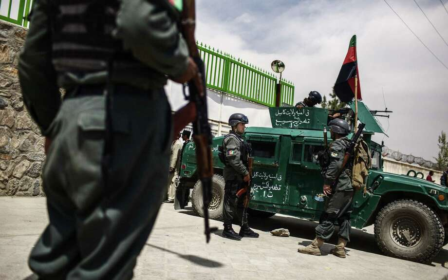 Afghan police stand guard outside with a security vehicle at Cure International Hospital after three American doctors were killed there Thursday morning in Kabul. Photo: Diego Ibarra Sanchez / New York Times / NYTNS