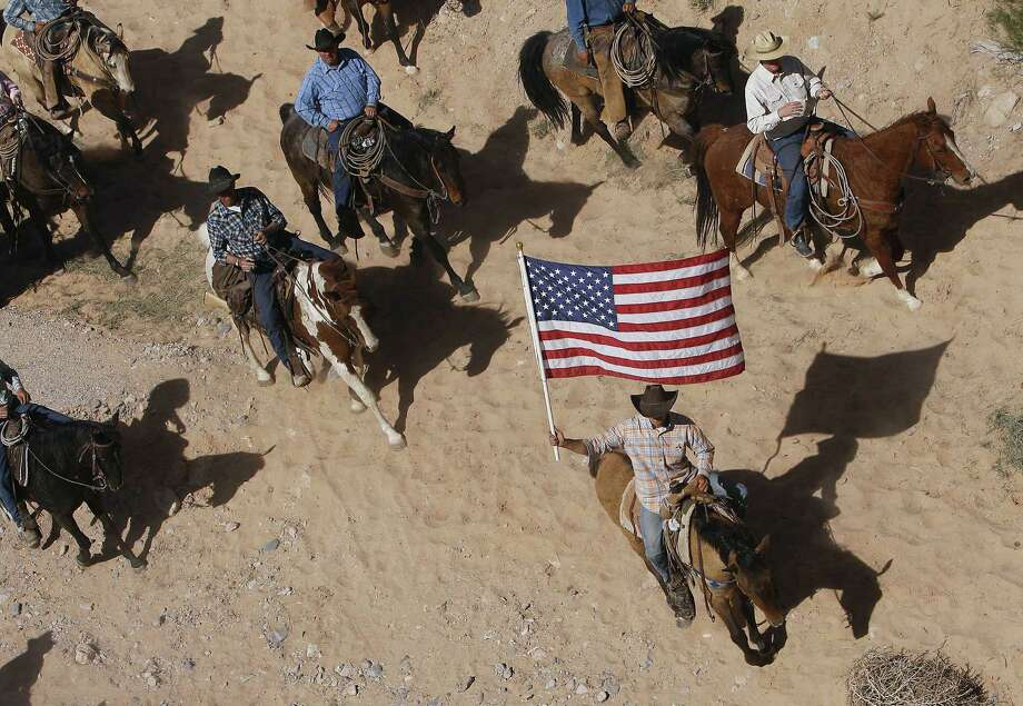 Cliven Bundy's supporters fly the U.S. flag as his cattle is released by the Bureau of Land Management back onto public land outside Bunkerville, Nev. Photo: Jason Bean / Associated Press / Las Vegas Review-Journal