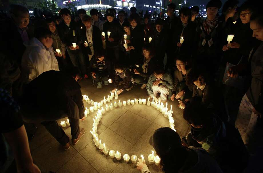 A candlelight vigil is held for the passengers of the sunken ferry Sewol in Ansan, South Korea. Angry relatives of people still missing accosted the fisheries minister and the coast guard chief Thursday. Photo: Lee Jin-man / Associated Press / AP