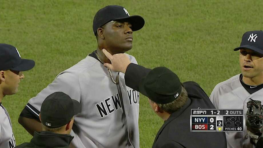 In this April 23, 2014 photo taken from video and provided by ESPN, home plate umpire Gerry Davis touches the neck of New York Yankees starting pitcher Michael Pineda in the second inning of the Yankees' baseball game against the Boston Red Sox at Fenway Park in Boston. Pineda was ejected after umpires found a foreign substance on his neck. (AP Photo/ESPN) ORG XMIT: NY158 / ESPN
