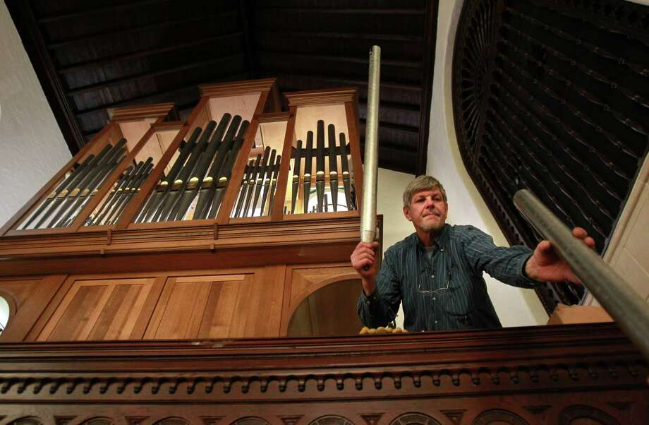 Martin Pasi reaches for metal pipes to set inside the new organ at First Evangelical Church on March 19, 2014, in Houston, Tx. Photo: Mayra Beltran, Houston Chronicle / © 2014 Houston Chronicle