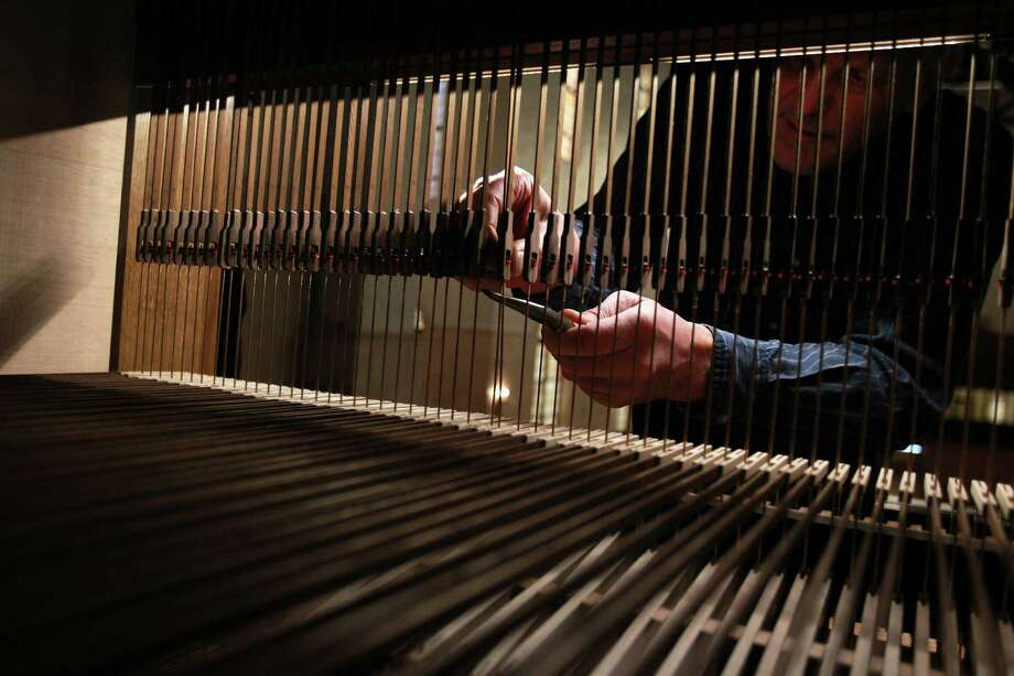 Martin Pasi tweaks sound by pinching the trackers of the pipe organ at First Evangelical Church on March 19, 2014, in Houston, Tx. Photo: Mayra Beltran, Houston Chronicle / © 2014 Houston Chronicle