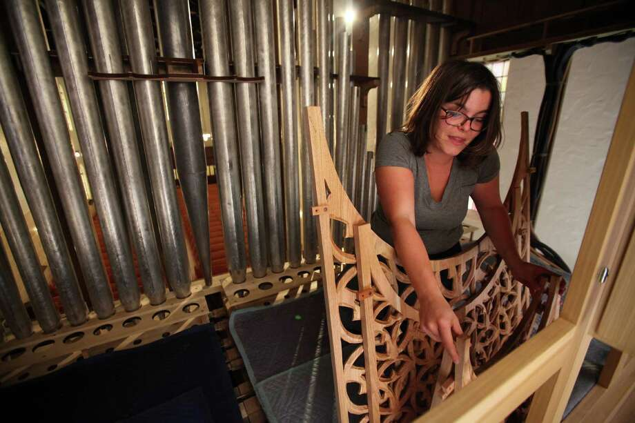 Maurine Pasi picks the decorative panel which will be set in place on the new pipe organ at First Evangelical Lutheran Church on March 19, 2014, in Houston. Photo: Mayra Beltran, Houston Chronicle / © 2014 Houston Chronicle