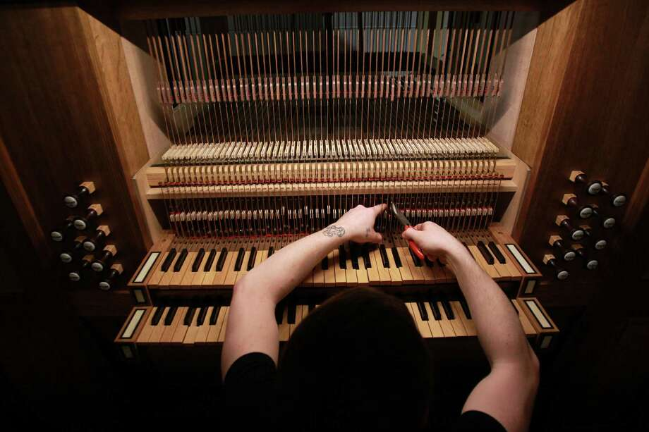 Steven Jett tweaks sound by pinching the trackers of the pipe organ at First Evangelical Church on March 19, 2014, in Houston, Tx. Photo: Mayra Beltran, Houston Chronicle / © 2014 Houston Chronicle