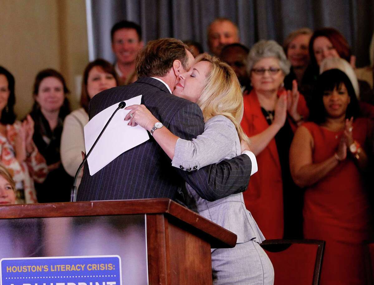 Neil Bush, chairman of the literacy foundation, hugs Julie Baker Finck, president of the foundation, during Thursday's news conference.