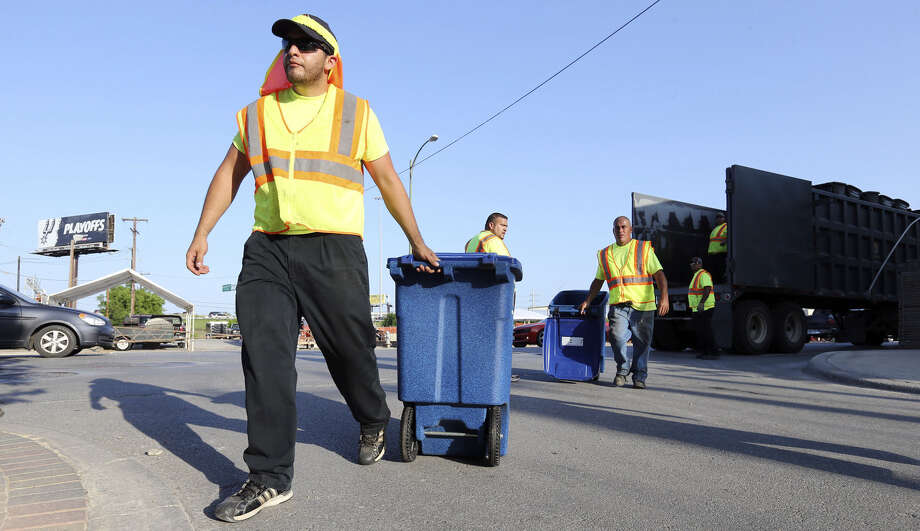 City workers Rudy Esquivel (from left), Raul Pena, Henry Flores and others set up recycling and trash bins Thursday on Broadway. Photo: Edward A. Ornelas / San Antonio Express-News / © 2014 San Antonio Express-News