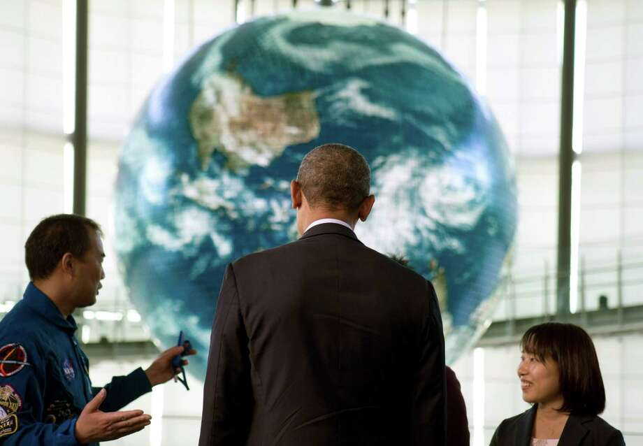 President Barack Obama stands in front of a huge display of planet earth as he attends a youth science event at the National Museum of Emerging Science and Innovation, known as the Miraikan, in Tokyo, Thursday, April 24, 2014. Showing solidarity with Japan, Obama affirmed Thursday that the U.S. would be obligated to defend Tokyo in a confrontation with Beijing over a set of disputed islands, but urged all sides to resolve the long-running dispute peacefully. (AP Photo/Carolyn Kaster) ORG XMIT: JPNK134 Photo: Carolyn Kaster / AP