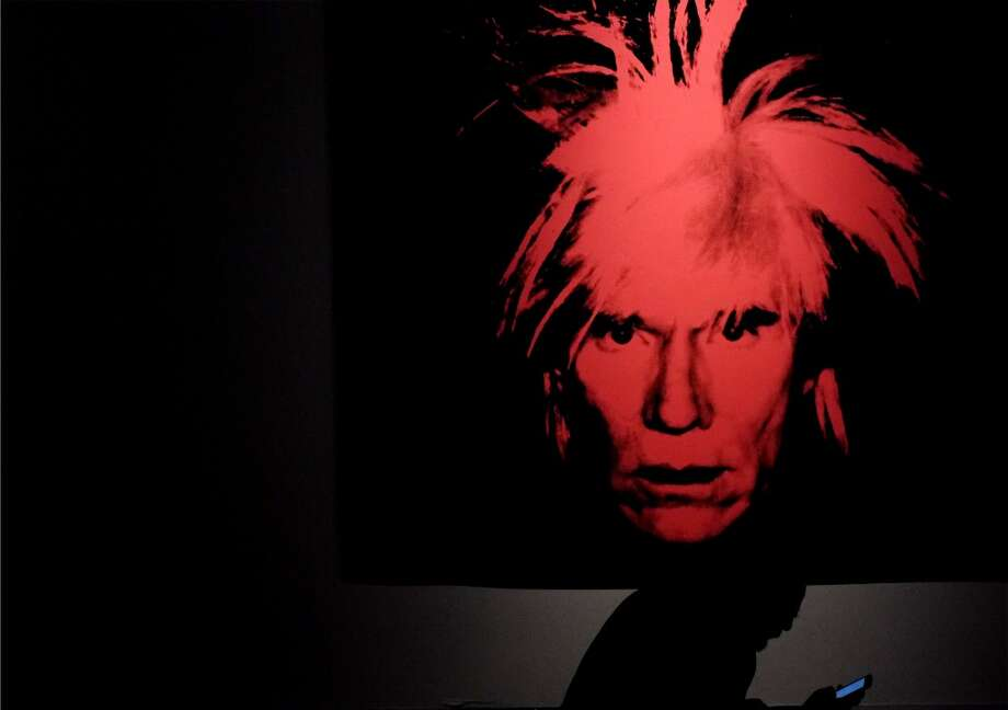 "A man seats in front of a selfportrait by US artist Andy Warhol as part of the exhibition ""Warhol"" on April 17, 2014 in Rome. The works of the artist, father of American Pop Art, will be housed in the renovated rooms of the Museo della Fondazione Roma, Palazzo Cipolla from April 18 until September 28, 2014. The exhibition features over 150 works, paintings, photographs and sculptures from the collection of Warhol's friend Peter Brant. The works on display range from Warhol's early drawings right up to his Last Supper series, first presented in Milan in 1987 in what was to be his last exhibition before his death that same year. Photo: ALBERTO PIZZOLI, AFP/Getty Images"