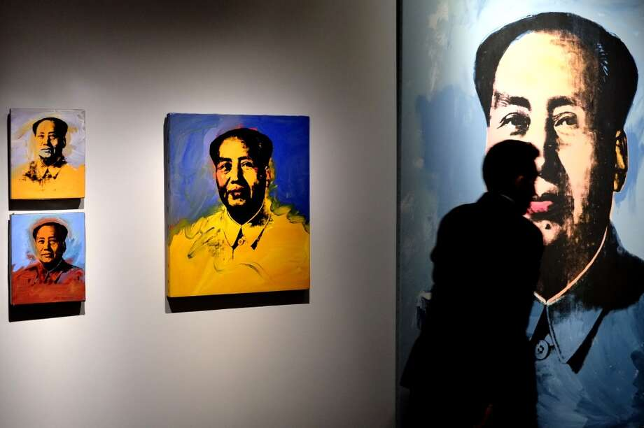 "A man looks at the ""Mao"" series, paintings by US artist Andy Warhol as part of the exhibition ""Warhol"" on April 17, 2014 in Rome. The works of the artist, father of American Pop Art, will be housed in the renovated rooms of the Museo della Fondazione Roma, Palazzo Cipolla from April 18 until September 28, 2014. The exhibition features over 150 works, paintings, photographs and sculptures from the collection of Warhol's friend Peter Brant. The works on display range from Warhol's early drawings right up to his Last Supper series, first presented in Milan in 1987 in what was to be his last exhibition before his death that same year. Photo: ALBERTO PIZZOLI, AFP/Getty Images"