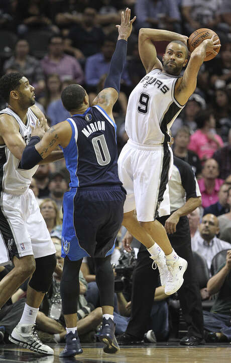 Tony Parker, passing around the Mavs' Shawn Marion, scored just 12 points on 5-of-10 shooting in the Spurs' Game 2 loss Wednesday at the AT&T Center. Photo: Jerry Lara / San Antonio Express-News / ©2014 San Antonio Express-News
