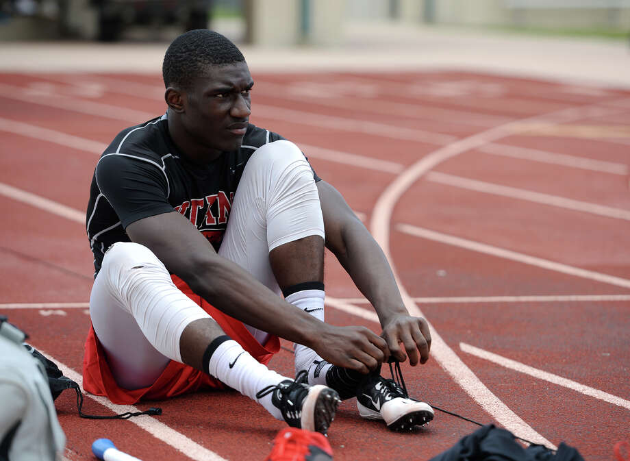 Corey Dauphine laces up his shoes for practice at the Memorial High School track Wednesday afternoon. Dauphine, a junior at Memorial High School in Port Arthur, competes in the 200 meter dash and on the relay team.