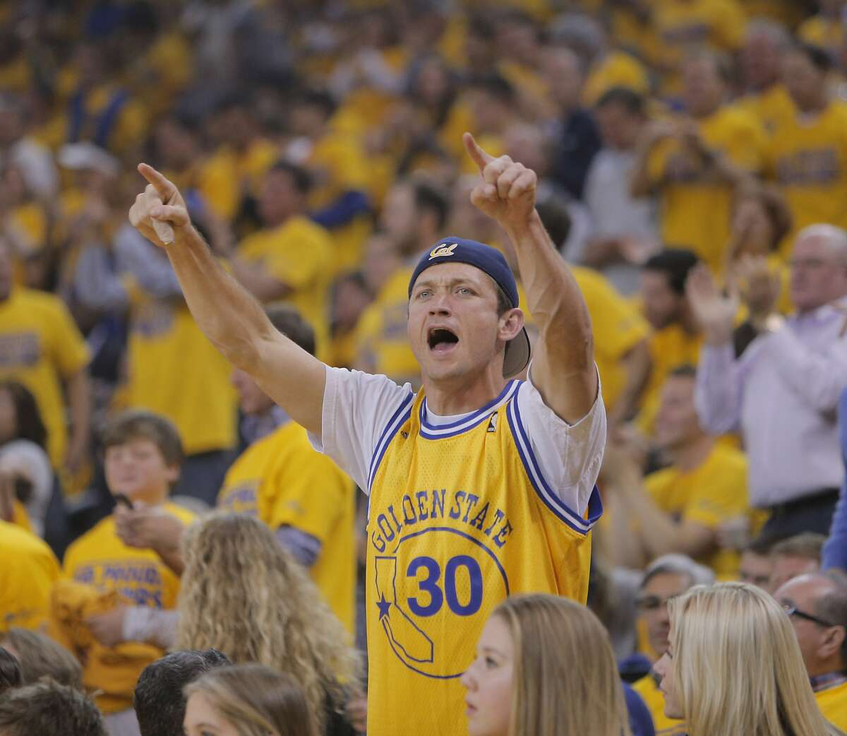 A Warriors fan reacts to a made shot by the Warriors in the first half. The Golden State Warriors played the Los Angeles Clippers at Oracle Arena in Oakland, Calif., on Thursday, April 24, 2014, in Game 3 of the first-round playoff series.