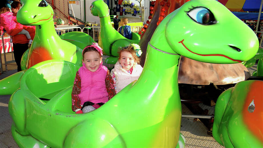 Sisters Ella and Julia Leavy, ages 5 and 3, of Fairfield, on the Dino ride Thursday of McKinley Elementary PTA's Spring Carnival at Jennings Beach. Photo: Mike Lauterborn / Fairfield Citizen