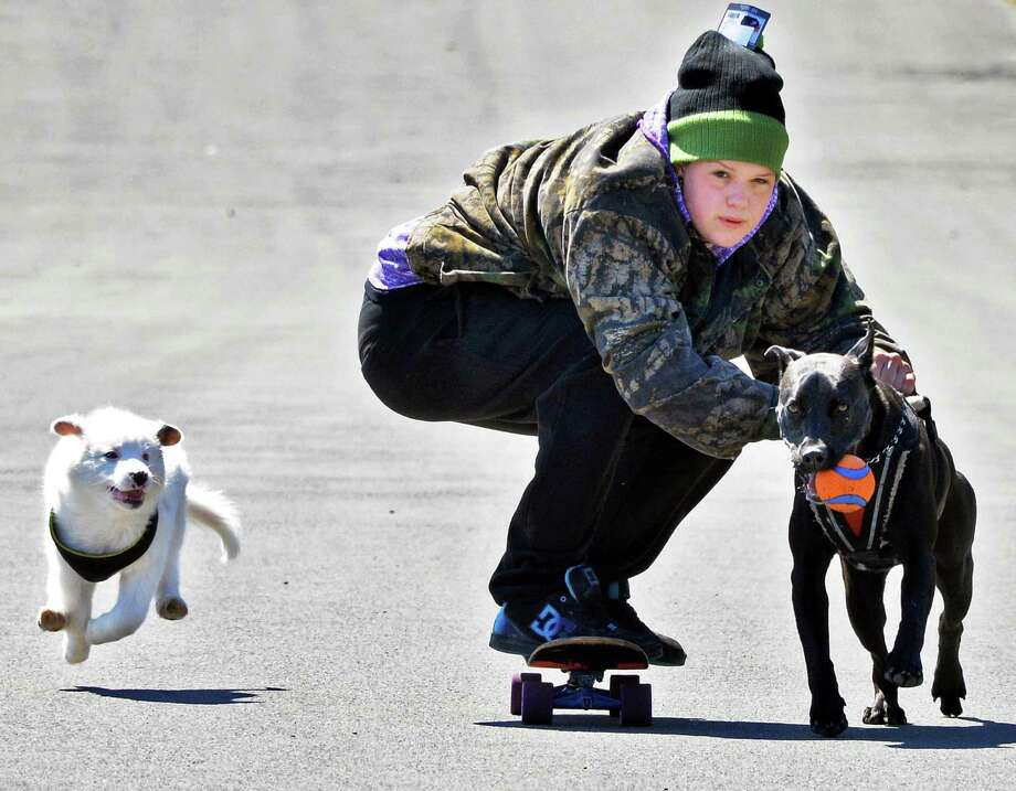 Shayla Norkun of South Bethlehem skateboards with dogs Gus, left, and Thor at Thatcher State Park Thursday April 24, 2014, in Voorheesville, NY.  (John Carl D'Annibale / Times Union) Photo: John Carl D'Annibale, Albany Times Union