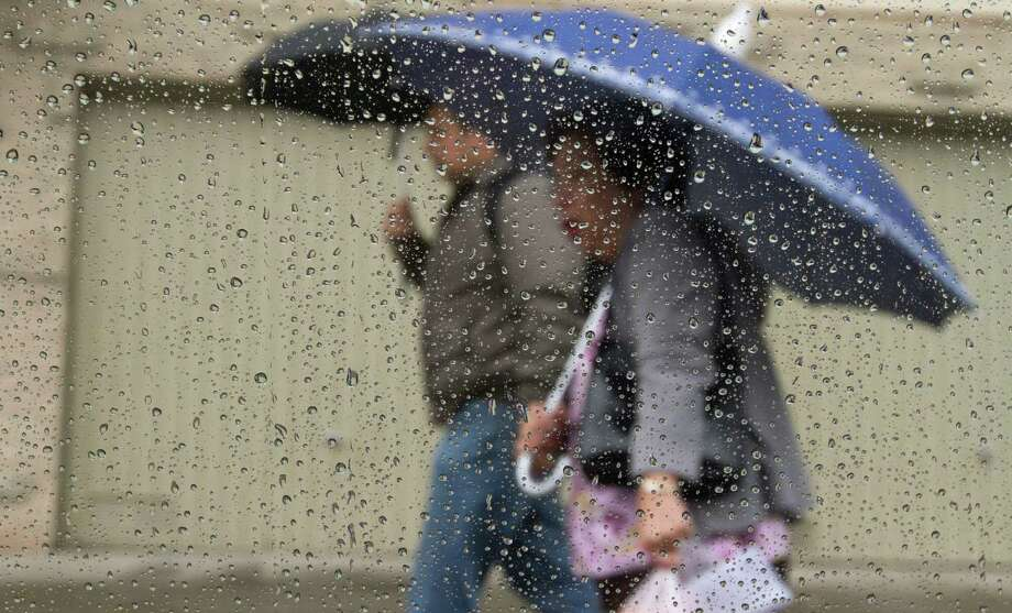 Pedestrians take cover under umbrellas during a rain shower in Oakland on Friday April 25, 2014. Photo: SF Gate / Douglas Zimmerman