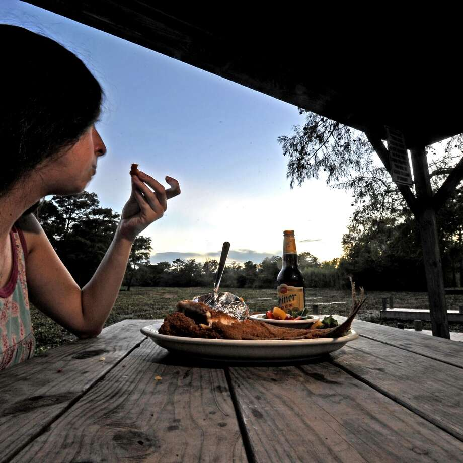 Brieann Fiorenza watches the sunset at Pine Tree Lodge in LaBelle with their famous catfish platter and a bucket of beer. Photo taken Wednesday, September 19, 2013. Photo taken: Randy Edwards/The Enterprise Photo: Beaumont Enterprise