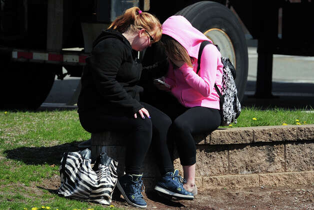 Two students comfort each other near Jonathan Law High School, in Milford, Conn. April 25, 2014, where Maren S