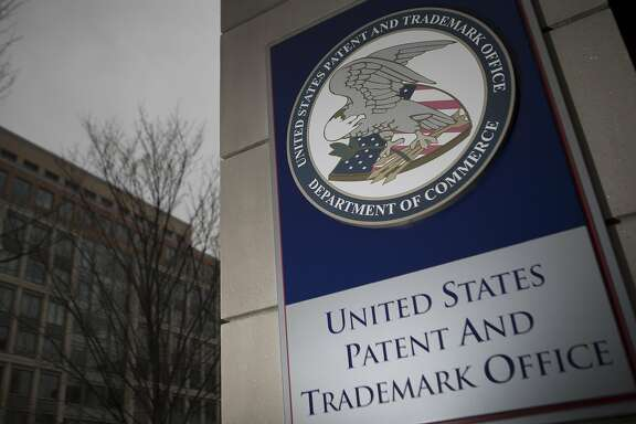 The U.S. Patent and Trademark Office (USPTO) seal is displayed outside the headquarters in Alexandria, Virginia, U.S., on Friday, April 4, 2014. The Senate Judiciary Committee tomorrow plans to mark up a measure that would curb the activities of so-called patent trolls after pulling back the bill last week in the face of opposition from such companies as 3M Co., AstraZeneca Plc, Monsanto Co. and Procter & Gamble Co. Photographer: Andrew Harrer/Bloomberg