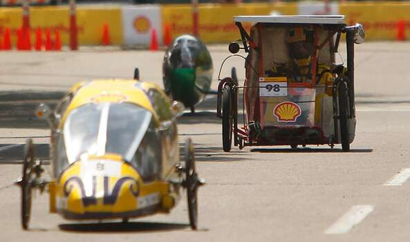 San Antonio's James Madison High School prototype vehicle  circles the track around Discovery Green park in downtown Houston during the 2012 Shell Eco-Marathon Americas. High school and college students test vehicles they have designed and built to see which can go the farthest distance using the least amount of fuel. Photo: Mayra Beltran, Houston Chronicle