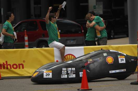 Felipe Arce Boiarski throws hands in the air as Vitor Trentini Neto embraces Andre William Tonatto, of Brazil's Unioeste-Universidade Estadual Do Oeste Do Parana, as their driver arrives to the pit upon completing laps during the 2012 Shell Eco-Marathon Americas. High school and college students test vehicles they have designed and built to see which can go the farthest distance using the least amount of fuel. Photo: Mayra Beltran, Houston Chronicle
