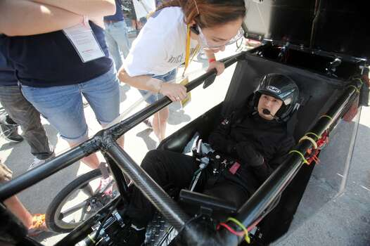 Driver Kerry Wang, 23, gets last minute instructions from the Rice University team during the 2012 Shell Eco-Marathon Americas. High school and college students test vehicles they have designed and built to see which can go the farthest distance using the least amount of fuel. Photo: Mayra Beltran, Houston Chronicle