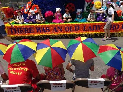Kids wear umbrella hats to watch the Battle of Flowers parade on Friday, April 25, 2014. Photo: Kin Man Hui, San Antonio Express-News