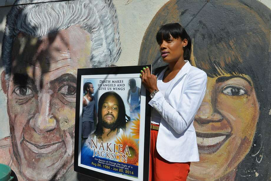 Shackelia Jackson-Thomas holds a poster showing her brother, Nakiea Jackson. The 27-year-old cook was killed by police in the capital, Kingston. Photo: Associated Press