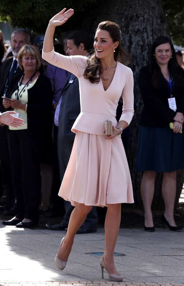 The Duchess waves to members of the crowd as she arrives with Prince William at the Playford Civic Centre in the Adelaide suburb of Elizabeth on April 23, 2014 in Adelaide, Australia. In typical Middleton style, another skirt suit, this time in pale pink with pleats. Photo: Pool, Getty Images