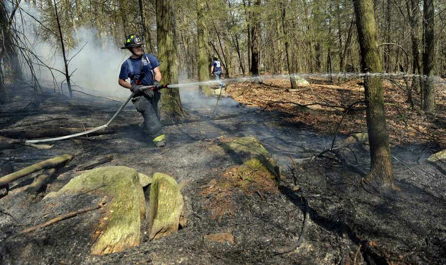 Firemen battle a brush fire off of Bear Moutain Road in Danbury, Conn. Friday, April 25, 2014. Photo: Carol Kaliff / The News-Times