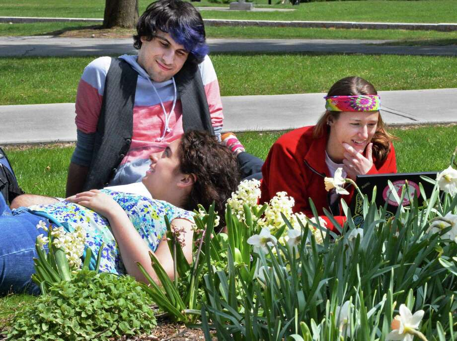RPI students Evan Plunkett, top, of Ipswich, Mass., Cori Rose Schroer of Vineland, NJ, and Geanette Orton, right, of Saranac, NY, take their Utopian Lit classwork outdoors  Friday April 25, 2014, in Troy, NY.  (John Carl D'Annibale / Times Union) Photo: John Carl D'Annibale