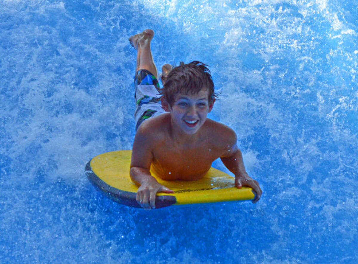 A visitor to Schlitterbahn Waterpark & Resort rides the Boogie Bahn, a surfing ride that uses a FlowRider wave simulator.