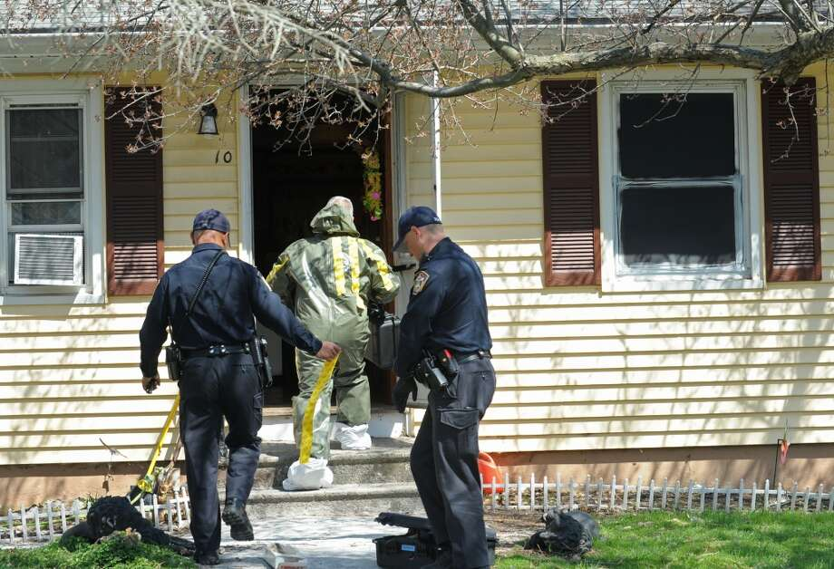 Detective Nihill enters the scene at 10 Eleanor Road in Seymour, Conn. in a hazmat suit on Friday, April, 25, 2014. Arthur Gauvin was arrested after his sister Nancy was found being held in the house.The window to the right is painted black and is where Nancy was allegedly held. Photo: Cathy Zuraw