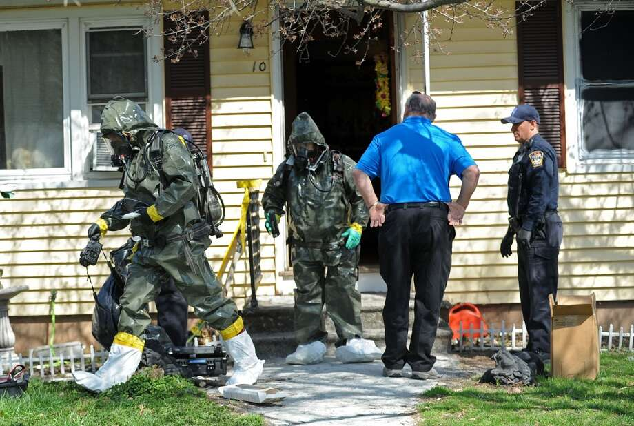 Police officers in hazmat suits come out the house at 10 Eleanor Road in Seymour, Conn. on Friday, April, 25, 2014. Arthur Gauvin was arrested after his sister Nancy was found being held in their home. Photo: Cathy Zuraw