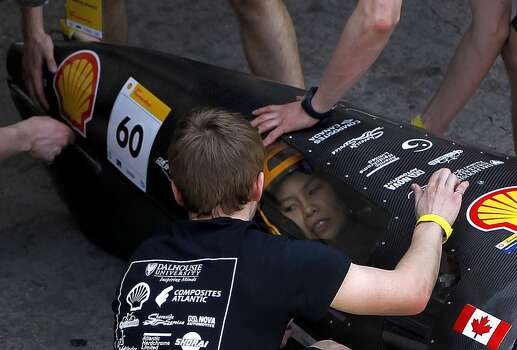 Members of the Dalhousie University iteam from Nova Scotia help to secure driver Allison Chua into the vehicle for a test run at Shell's Eco-marathon Americas competition at the George R. Brown Convention center in downtown Houston in April 2014. College and high school student teams from across the Americas compete with their futuristic, super-mileage vehicles searching for solutions to make transportation more efficient while reducing environmental impact. Photo: Karen Warren, Houston Chronicle