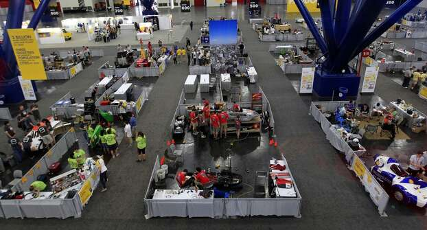 Students work on their vehicles for Shell's Eco-marathon Americas competition at the George R. Brown Convention center in downtown Houston in April 2014. College and high school student teams from across the Americas compete with their futuristic, super-mileage vehicles searching for solutions to make transportation more efficient while reducing environmental impact. Photo: Karen Warren, Houston Chronicle