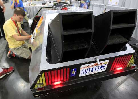 """Marcus Garner, 16, with St. Paul's School in Louisiana, works to wire the turn signals on his team's prototype  """"DeLorean"""" at Shell's Eco-marathon Americas competition at the George R. Brown Convention center in downtown Houston in April 2014. College and high school student teams from across the Americas compete with their futuristic, super-mileage vehicles searching for solutions to make transportation more efficient while reducing environmental impact. Photo: Karen Warren, Houston Chronicle"""