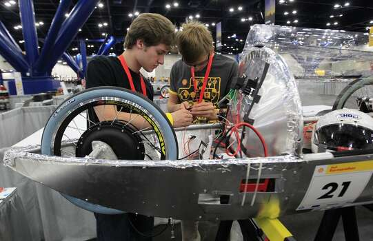 Richard Appel, 16 (left), and Jake Peacock, 18,  of St. John's School in Houston, work on wiring their team's prototype car at Shell's Eco-marathon Americas competition at the George R. Brown Convention center in downtown Houston in April 2014. College and high school student teams from across the Americas compete with their futuristic, super-mileage vehicles searching for solutions to make transportation more efficient while reducing environmental impact. Photo: Karen Warren, Houston Chronicle