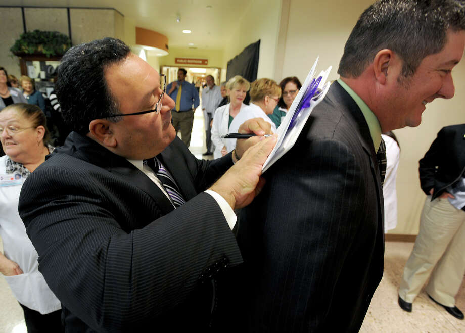 Shawn Adams holds still while Paul Trevino signs a letter that would be placed in a time capsule during Christus St. Elizabeth's 50th anniversary celebration on Thursday. The letter is expected to be read by those who open the capsule in 2037.  Photo taken Thursday, November 15, 2012 Guiseppe Barranco/The Enterprise Photo: Guiseppe Barranco, STAFF PHOTOGRAPHER / The Beaumont Enterprise